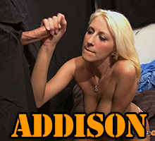 Addison strokes a cock that sticks out through a glory hole