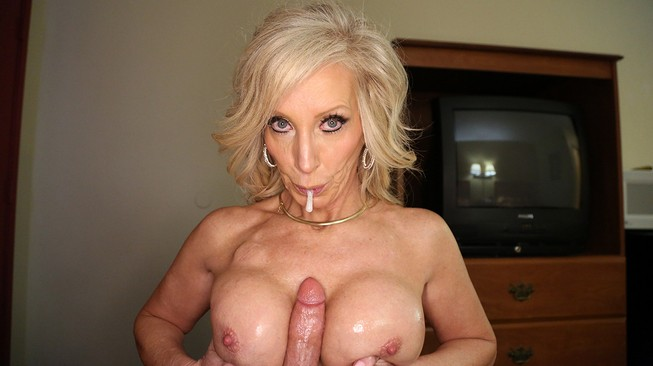 Lubes his cock and her boobs for a titjob